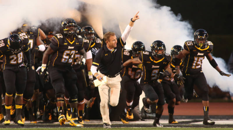 Head coach Rob Ambrose leads the Tigers onto the field for Saturday's home opener against Delaware State.